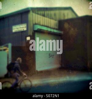 A man in a bike rides past a industrial unit - Stock Photo