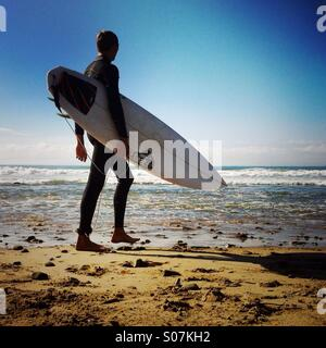 A surfer walks up the beach. Ventura California USA. - Stock Photo