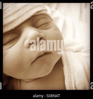 Close up of newborn baby boy with a hat on - Stock Photo