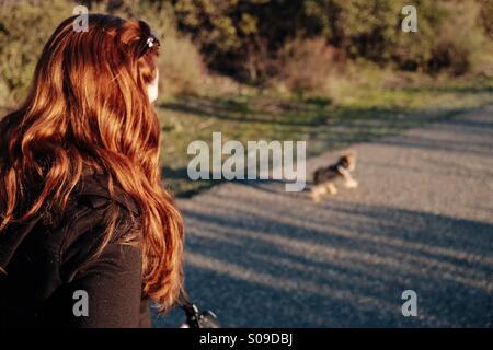 Redhead walking dog - Stock Photo