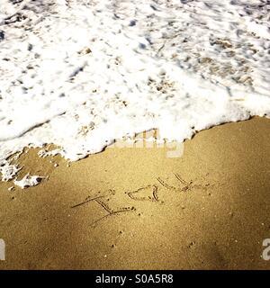 I love u written in the sand at the shoreline. Manhattan Beach, California USA. - Stock Photo