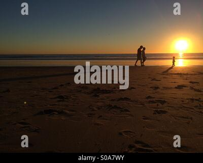 Family walking on the beach during sunset. - Stock Photo