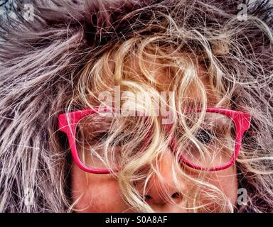 Young Girl wearing furry hood with face obscured by curly blind hair - Stock Photo