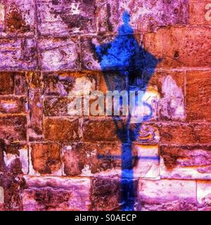 Shadow of old lamp on stone wall England UK - Stock Photo