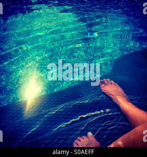 Woman sitting on pool's edge, feet in the water. - Stock Photo