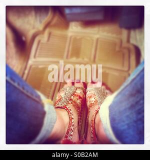 Looking down on blue jeans and painted red toes in ethnic beaded sandals on top of beige plastic Matt in a car. - Stock Photo