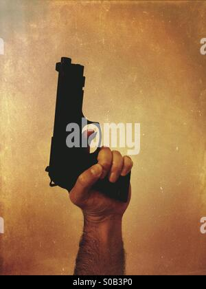 Criminal holding a gun - Stock Photo