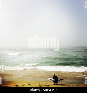 A surfer waits on the beach. Manhattan Beach, California USA. - Stock Photo