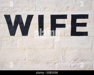 Wife written in black paint on white painted brick wall - Stock Photo