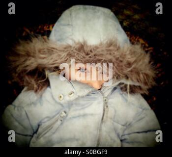 Young girl peeping out from under furry coat hood - Stock Photo