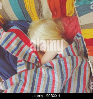 Young blond girl asleep wrapped in a number of brightly colored blankets. - Stock Photo