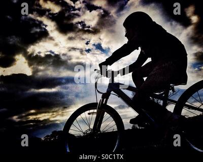 Young girl on bike in silhouette against dramatic sky - Stock Photo