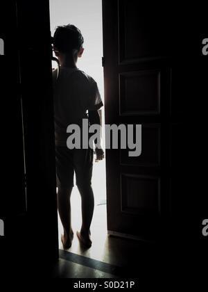 Little boy by the door - Stock Photo