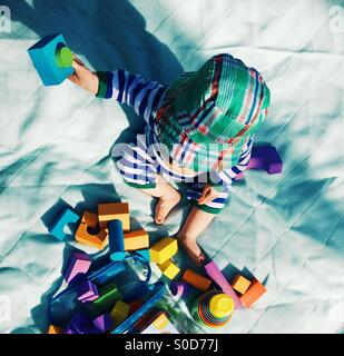 9 month old baby boy plays with foam blocks on a picnic blanket in the garden in the sunshine - Stock Photo
