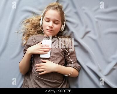 It sounds like a dream. Young girl lying on the bed and dreaming about something with closed eyes. - Stock Photo