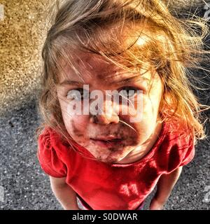 Child with a dirty face and windswept hair looking up - Stock Photo