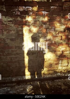 Shadow of a little boy on a brick wall - Stock Photo