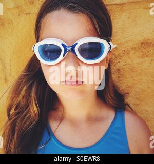 Girl, wearing swimming goggle and a blue swimsuit. - Stock Photo