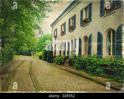 View of Maison du Jardinage with pretty blue shutters at Parc de Bercy in Paris, France. Brick pavement, trees and - Stock Photo