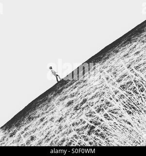Boy walking up hill - Stock Photo