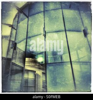 Old building reflected in modern building's glass front. - Stock Photo