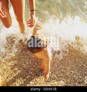Mother and baby girl on beach top view - Stock Photo