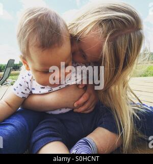 Young girl kissing and hugging her baby brother - Stock Photo
