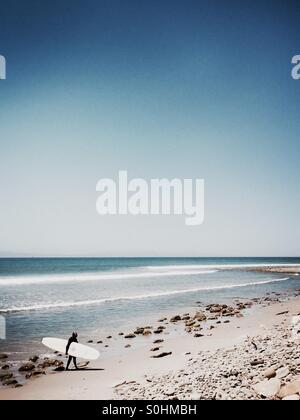 A surfer walks up the beach. Ventura, California USA. - Stock Photo