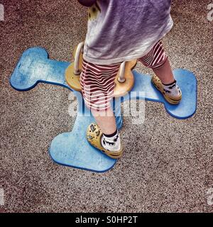 Young boy balancing on playground ride - Stock Photo