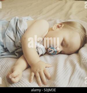 8 month old baby boy sleeping peacefully on a hot summer day on parents bed covered with a light blue blanket, with - Stock Photo
