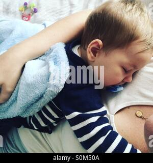 Tired 9 months old baby boy taking a nap on top of his mom . - Stock Photo