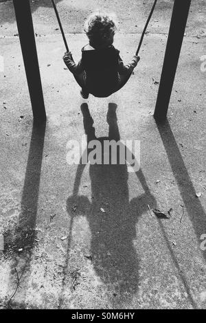 Boy on swing with long shadows - Stock Photo
