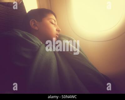 Boy sleeping on the plane - Stock Photo