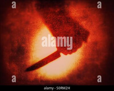 Shadow of hand gripping knife against blood red background - Stock Photo