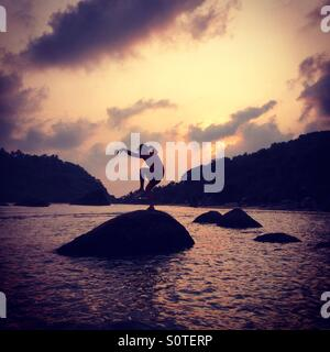 Man balancing on rocks in the sea on Palolem Beach, Goa - Stock Photo