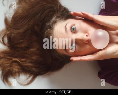 Funny image of a young woman blowing a bubble gum bubble - Stock Photo