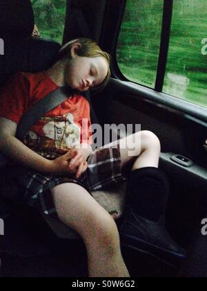 Boy sleeping in car during road trip - Stock Photo