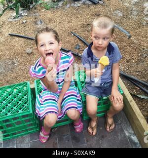 Little girl and little boy eating ice cream - Stock Photo
