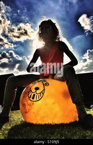 Young girl bouncing on retro Space Hopper toy - Stockfoto