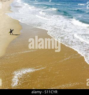 A lone surfer walks up the beach.  Manhattan Beach, California USA. - Stock Photo