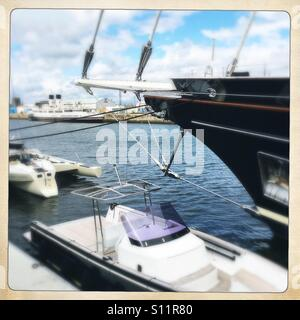 Bowsprit of super yacht 'Eos' with tender foreground and TS Queen Mary background. Greenock Scotland - Stock Photo