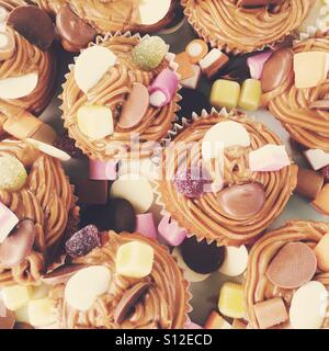 Chocolate cup cakes with dolly mixtures on top - Stock Photo