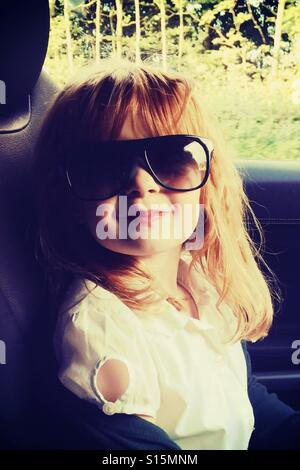 Young 6 year old girl wearing sunglasses smiling - Stockfoto
