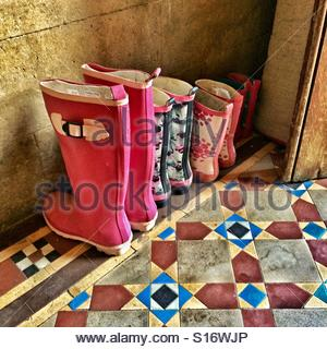 A family's Wellington boots lined up at the door - Stock Photo