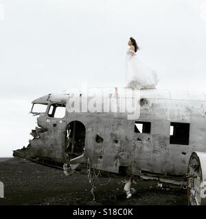 Girl in a wedding dress on top of a plane wreck in Iceland - Stock Photo