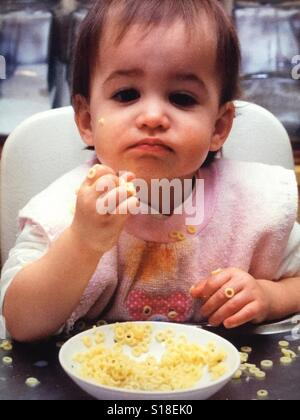 An infant girl in a high chair messily eating noodles - Stock Photo