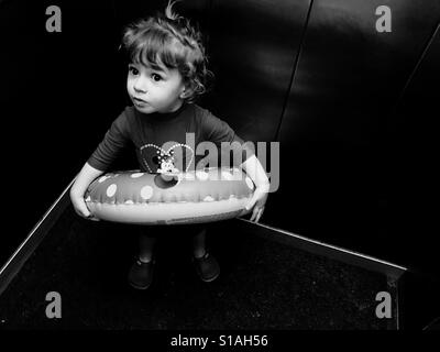 Girl with inflatable ring going to the swimming pool - Stock Photo