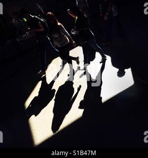 Passengers walk through a beam of light thrown on the platform of San Antonio metro station in Medellín, Colombia, - Stock Photo