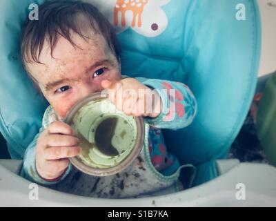 Baby eating messily - Stock Photo