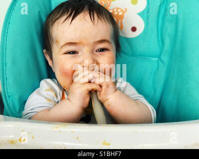 7 months old baby eating by himself - Stock Photo